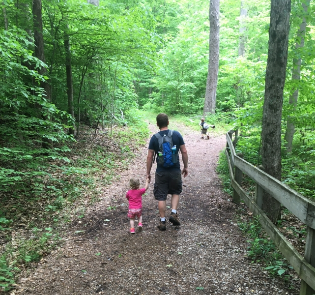 my two kids and husband on a forest trail