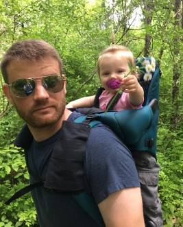 dad hiking with daughter in carrier holding flowers