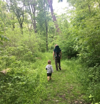 son hiking while dad carries daughter