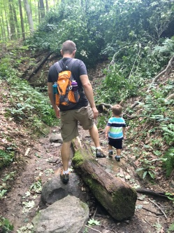 dad and son hiking down a ravine